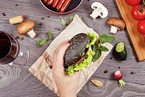 Black burger in men's hand