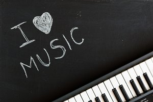 Music keyboard on blackboard background for music school children