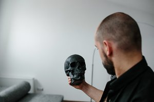 bearded man holding skull