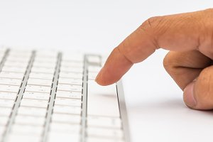 Hand typing white keyboard