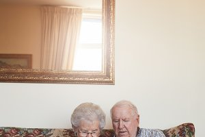 Retired couple at home using tablet