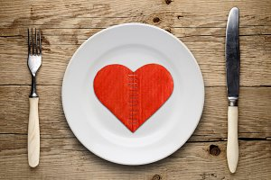 Broken cardboard heart on plate