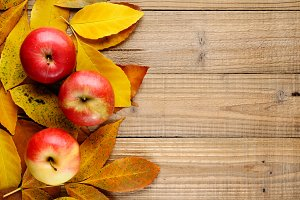 Three apples on autumn leaves