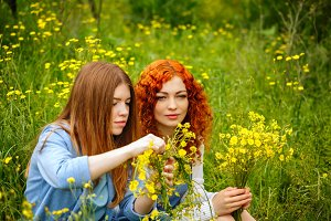 Girlfriends collect wildflowers.