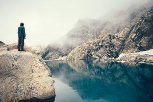 Man Traveler on stone cliff lake