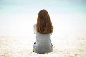Lonely woman sit down on beach