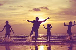 Happy family dancing on the beach.