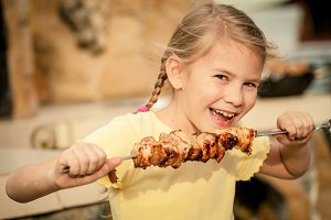 Little girl eating outdoors.