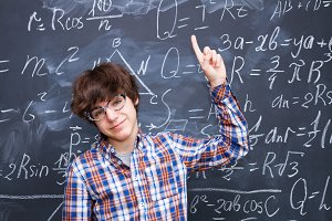Boy and blackboard filled with math formulas