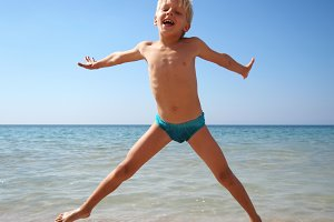 boy jumping on a sea