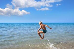 boy jumping on a sea