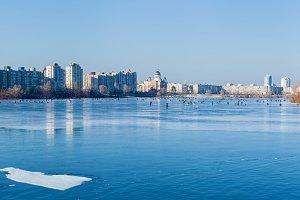 Quay in Kiev frozen lake in the urban landscape, man on winter f