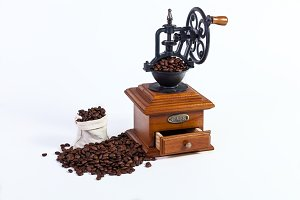 an old hand grinder for grinding coffee beans, roasted coffee beans on a white background.