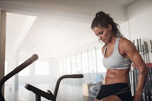 Fitness woman sitting on gym bicycle