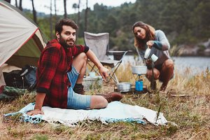 Couple camping outdoors by the lake