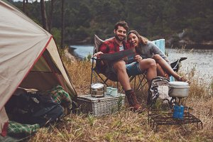 Loving couple camping by the lake