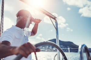 Mature man at the wheel of a yacht
