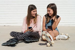 two girls with smartphone laughing
