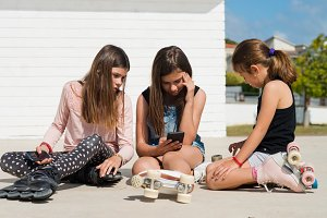 three girls play on the phone