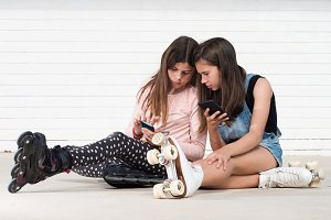 two girls playing with smartphone