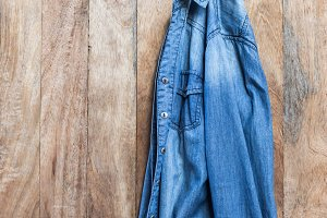 blue jeans jacket on wooden