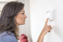 Woman turn on the thermostat.