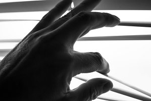 Silhouette of man's hand opens the shutters B&W, shallow depth of field