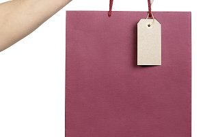 paper bag with a price tag in hand