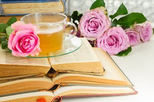 Cup of tea with books and roses