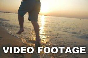 Feet of Boy Running on the Beach