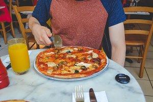 Man's hand cutting pizza