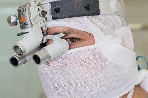 Surgeon with binocular headband magn