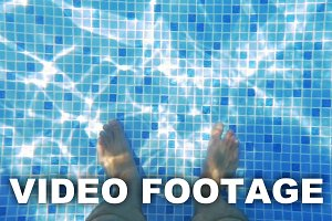 Man Feet in Sunlit Swimming Pool