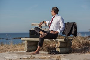 Businessman resting on a bench