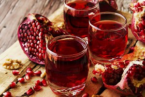 Fresh pomegranates and juice, selective focus