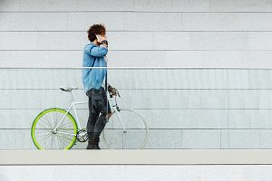 Young man with bicycle using mobile.