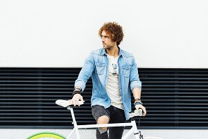 Young man with bicycle in the city.