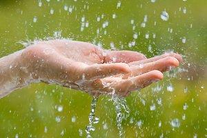 hand of woman catching raindrops