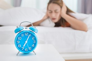 Girl looking at alarm clock