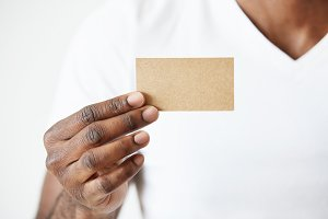Confident African entrepreneur in white T-shirt giving business card to you. Close up view of black male hands holding blank business card for your information or promotional content. Selective focus