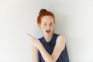 Portrait of young redhead female with perfect freckled skin showing something interesting at copy space wall for your information or advertising content, winking at the camera and pointing sideways