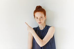 Young redhead female in spotted dress pointing a finger at blank wall with copy space for your text or product advertisement, looking at the camera with serious expression. Advertising concept