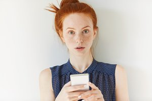 Pretty student girl with ginger hair and freckles holding mobile phone, typing or reading a message, texting online with friends via social networks, looking at the camera with serious expression