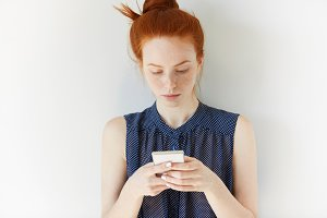 Headshot of teenage girl texting her friends using mobile phone. Young redhead woman in spotted dress holding cell phone, communicating online or reading news, using wireless Internet connection