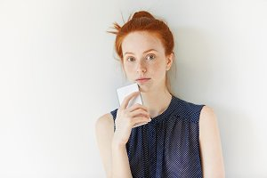 Portrait of beautiful Caucasian redhead girl browsing Internet on smart phone, looking at the camera. Young female freelancer with red hair using electronic gadget for working on her project indoor