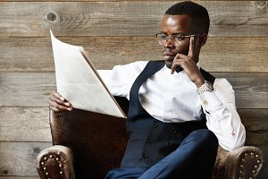 Confident African CEO in formal suit and glasses reading financial newspaper with concentrated expression, sitting in leather armchair against wooden wall in the morning. Business and success concept
