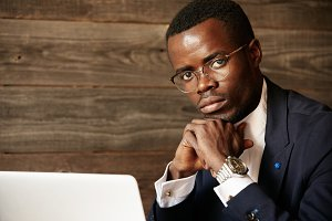 Portrait of successful confident young African entrepreneur wearing glasses and formal suit looking at the camera with serious and thoughtful expression. Black businessman working on laptop at cafe
