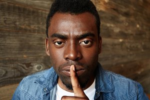 Headshot of young African man in stylish clothes holding finger on lips, asking to be quiet or keep silence, saying shh, looking at the camera with serious and concentrated expression. Body language
