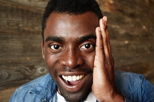 Close up portrait of happy handsome young black man looking in excitement at the camera, holding hands on cheeks with mouth wide open against wooden wall. Positive human emotions and facial expression