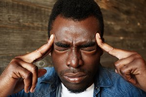 Close up portrait of worried young African American young man having bad headache pressing both hands on temples with eyes closed. Negative emotions, facial expressions and feelings. Body language